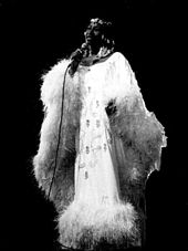 A woman in a white feathers' dress holding a microphone up her neck.
