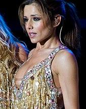 Com seu cabelo castanho amarrado para trás, uma mulher vestindo uma roupa brilhante está realizando com um microfone headset.