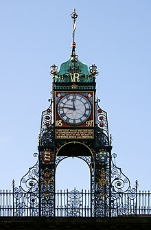 "A highly ornate structure in wrought iron, with a railing at the base.  It carries a clock with Roman numerals; this has a red frame bearing the date ""1897"" in gold, and under it is a plate with an inscription in gold lettering.  Above the clock are the initials ""VR"" in gold, and at the summit is a green cupola with a weather vane."