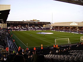A colour photograph of Craven Cottage football stadium, showing the pitch in the centre of the image, surrounded stands. At the top of the photo, the word 'Fulham' is spelt out in white lettering on a the black seats.