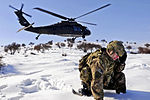 Defense.gov News Photo 120301-A-2444D-247 - U.S. Army Sgt. 1st Class Shawn Joyce shields his face from blowing snow and other debris as a UH-60 Black Hawk helicopter lands nearby in.jpg