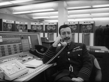 Sellers with neat hair and moustache in RAF uniform talking on the telephone