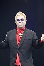 A blond-haired middle-aged man stands with his arms open and fists clenched. He wears a dark suit and red shirt. He also sports a cross pendant around his neck, and wears purple sunglasses.