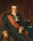 Portrait of a clean-shaven, square-faced man sitting in a chair. He wears a black suit with embroidered cuffs and a red sash over his right shoulder. Several awards are pinned to his coat.