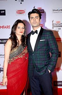 Fawad and Sadaf Khan, formally dressed and striking a serious pose