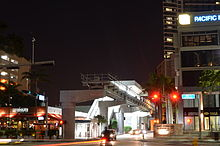 An elevated metro station at night with tall buildings on opposite sides.