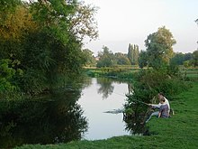 Photograph of a man and a child angling on the bank of the River Cam in the United Kingdom
