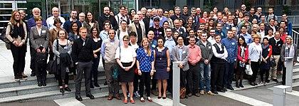 Skupina vědců na setkání pózuje venku