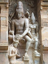 Granite sculpture of a devotee in kneeling posture garlanded by Shiva and Parvathi in sitting posture
