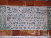A tablet formed of two large tiles, bordered by green flowers in the style of the Arts and Crafts movement