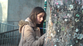Girl signing tree in Jim Morrison grave - Pere Lachaise.png