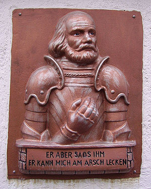 """Götz von Berlichingen (Goethe) - Representation of Götz with his famous quote: """"But he, tell him, he can lick my arse"""" from Goethe's play (plaque in Weisenheim am Sand)"""