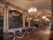 Vue d'une salle tout en longueur couverte de grandes toiles et comportant plusieurs meubles le long d'un des longs murs