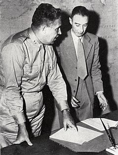 A man in shirt and tie and another wearing a suit stand behind a writing desk. On the wall behind is a map of the Pacific.