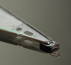 Close-up of a hard disk head resting on a disk...