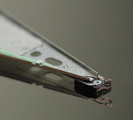 Close-up of an HDD head resting on a disk platter; its mirror reflection is visible on the platter surface. Hard disk head.jpg