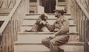 Henry Adams seated with dog on steps of piazza, photograph by Marian Hooper Adams, ca. 1883