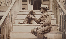 Henry Adams seated with dog on steps of piazza, photograph by Marian Hooper Adams, ca. 1883.jpg