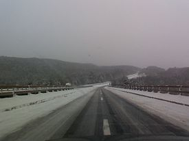 A snowy highway road that is icy and looking towards forests and mountains.