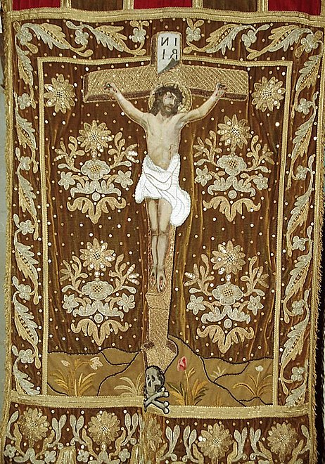 "A processional banner in the Sainte-Nonne church depicting Christ's crucifixion. Note the ""Ankou"" at the base of the cross."
