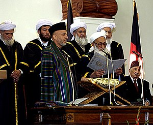 Politics of Afghanistan - Hamid Karzai standing next to Faisal Ahmad Shinwari and others after winning the 2004 presidential election. The last king of Afghanistan, Zahir Shah is sitting at the right.