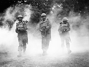 History of the Irish Guards - Irish Guards wearing gasmasks advance through smoke with 'tommy guns' at the ready, Nooks Head near Woking in Surrey, 8 July 1940.