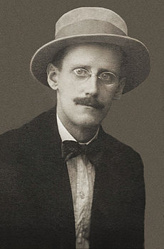 A black-and-white photographic portrait of a mustachioed man with glasses in a brimmed hat.