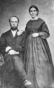 A balck and white photograph of a sitting balding man with a beard and a standing woman