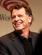 A 63-year old, dark-haired man, smiling at the left of the camera.