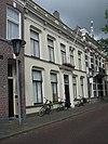 foto van Deftig herenhuis met kroonlijst met consoles en balustrade onder dwars zadeldak tussen puntgevels