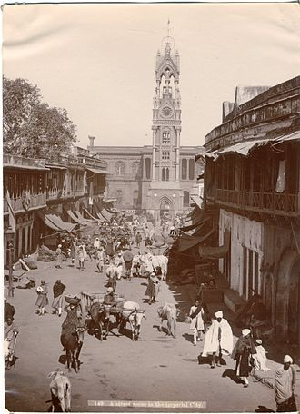 """Ghantaghar -  """"A street scene in the imperial City,"""" photo by Jadu Kissen, acquired by a visitor in 1910, as viewed from Nai Sarak"""