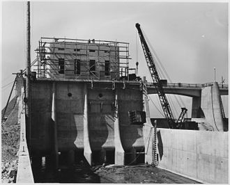 Sepulveda Dam - Looking upstream in the outlet channel. Form work has been stripped from the outlet control tower and service bridge and one of the outlet control slide gate frames is being lowered into position for installation.