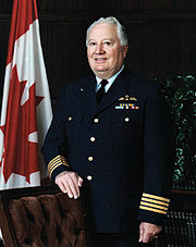 Canadian military officer standing in uniform beside Canadian flag