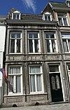 foto van Huis met brede lijstgevel, voorzien van vensters in Naamse steen, in verticale richting met elkaar verbonden door panelen.