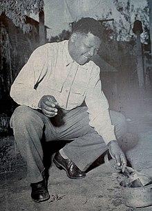 Mandela nell'atto di bruciare il suo pass book, un documento richiesto ai neri dalle leggi razziali (1960).