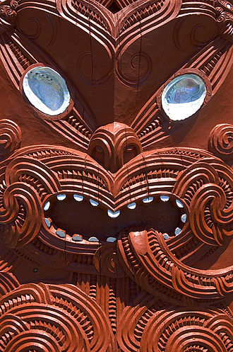 Tūmatauenga - A human face depicted in a house carving. Tūmatauenga, god of war, is the ancestor of humankind