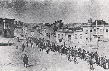 Civili armeni in marcia forzata verso il campo di prigionia di Mezireh, sorvegliati da soldati turchi armati. Kharpert, Impero Ottomano, aprile 1915.