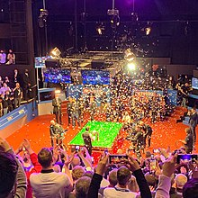 image of confetti falling on a snooker table as Selby holds a trophy
