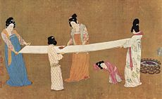Two women hold out a long bolt of white silk by the corners, while two other women brush out the silk with combs.