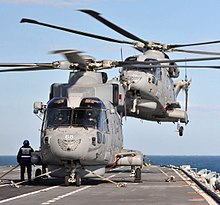 Two AgustaWestland Merlin HM2 of 814 NAS landing on HMS Illustrious during Exercise Joint Warrior near Scotland in 2012. Note the tiger markings on the aircraft noses.