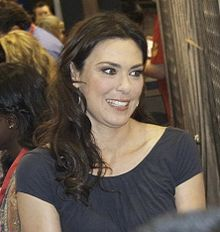 A Caucasian woman with brunette hair wears a dark grey blouse.