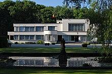 Bâtiment de style transition entre l'Art déco et le modernisme à la façade enduite de blanc et percée de nombreuses baies vitrées avec en son centre une avancée hémi-circulaire