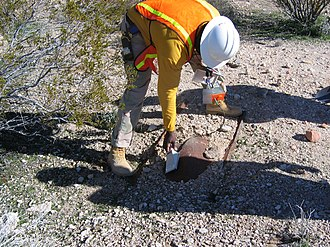 Scintillation counter - Scintillation probe being used to measure surface radioactive contamination. The probe is held as close to the object as practicable