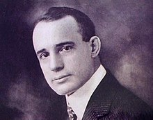 Photograph of head of young man clad in white shirt, jacket and tie.