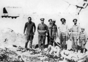 Eight men in dressed in military fatigues standing before an organized assembly of weapons, mostly rifles and mortar. The first man from the left is not wearing a hat, while the remaining seven are wearing hats.