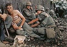Soldatoj atende nervoze per fusiloj proksime de muro.