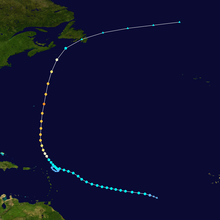 Track of a tropical cyclone, with different colors corresponding to differing intensities. The track begins to the right, moves left and then up, eventually crossing a land mass near the top of the image.