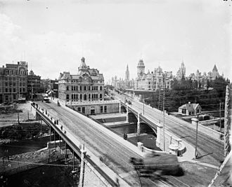 History of Ottawa - Old Ottawa Post Office. Sappers Bridge (left), Dufferin Bridge(right) over the Rideau Canal, 1890s.  Today the War Memorial stands where the post office stood, with a new post office (now also old) on Sparks Street. The two bridges were replaced by the Plaza Bridge (Ottawa), and filled in.  The centre block of the parliament buildings was replaced after a 1916 fire.