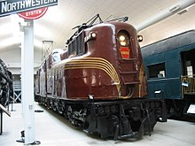 A burgundy locomotive, with gold stripes in a museum with other railroad equipment.