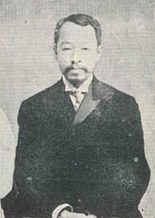 A monochrome photograph of a bearded Korean man in a suit